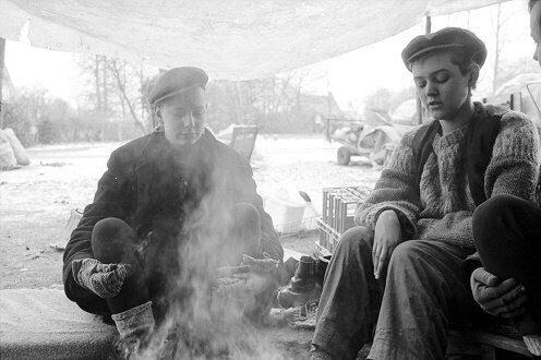 Two women sitting around a campfire in winter.